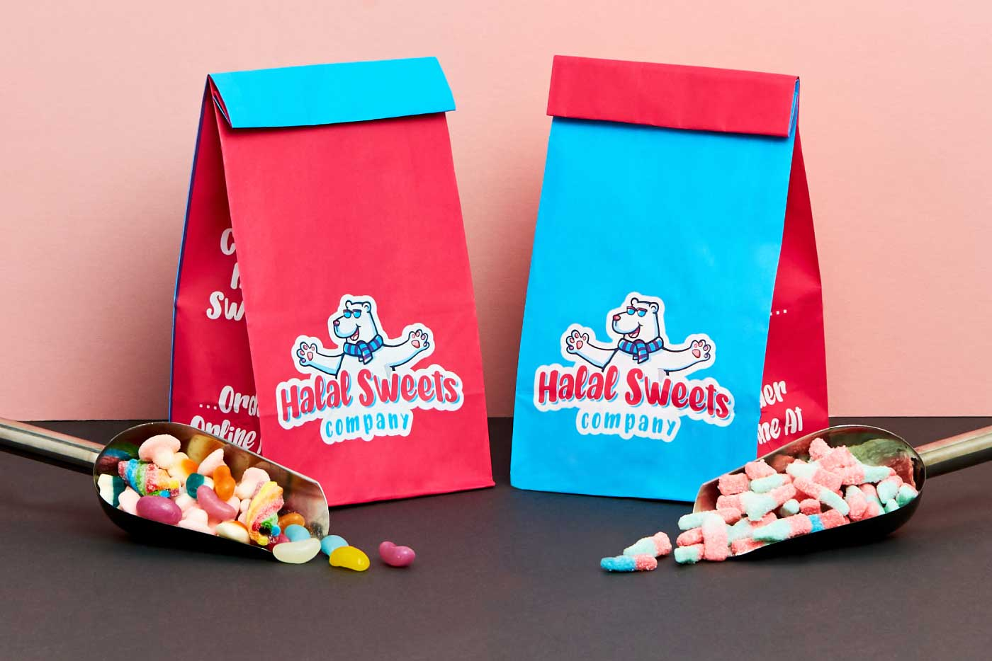 2 of Halal Sweets Company pink and blue Pick 'n' Mix bags stood side by side with 2 scoops (laid out symmetrically) holding a variety of tasty flavours by the side.